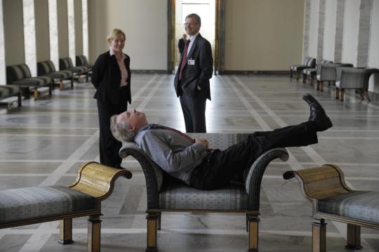 Uutiskuvaaja Martti Kainulainen maata rötköttää tuolilla eduskunnassa.