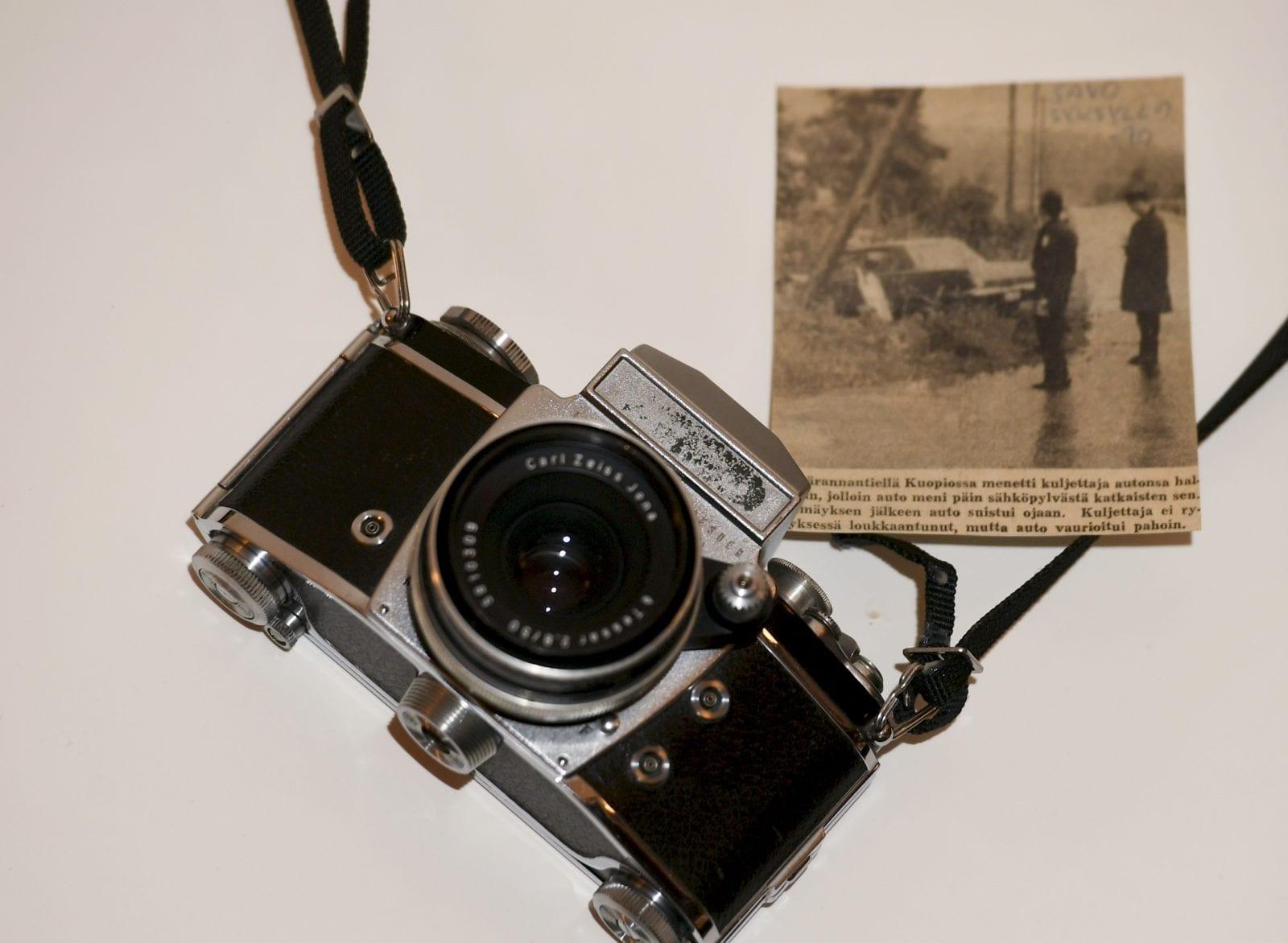 Vanha kamera ja lehtileike, jossa näkyvän kuvan Martti Kainulainen on kyseisellä kameralla ottanut.