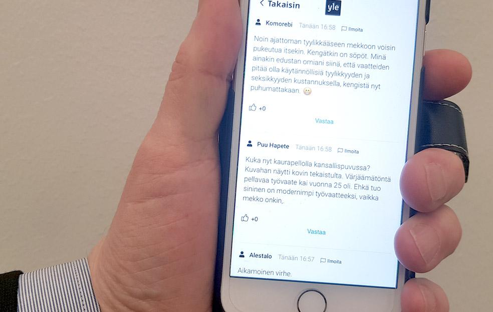 Miehen käsi pitelee kännykkää, jonka näytöllä on Ylen keskustelupalstan sisältöä.