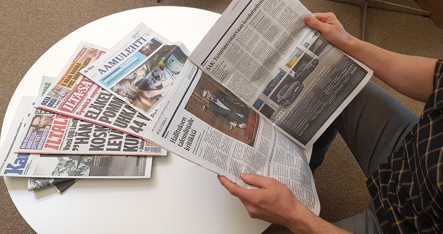 Mies lukee Helsingin Sanomia sanomalehtipino pöydällä vieressään.