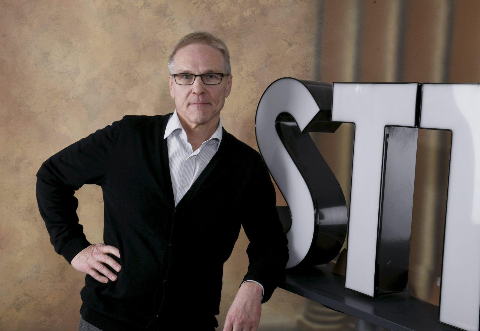 Kimmo Pietinen poseeraa STT:n logon edessä.