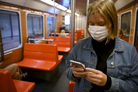Nuori nainen matkustaa metrossa kasvomaski naamallaan ja selaa puhelintaan.