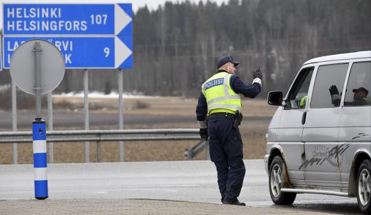 Poliisi tarkastamassa autoilijan kulkulupaa tarkastuspisteellä Uudenmaan rajalla huhtikuussa 2020.