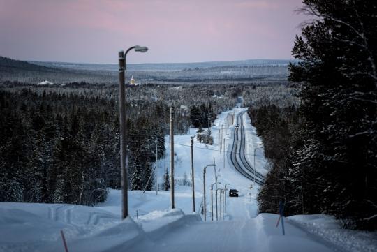 Yksinäinen auto ajaa lumisella tiellä metsäisessä maisemassa.