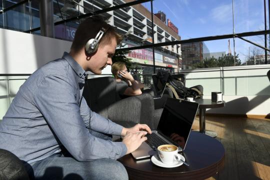 Kuulokkeita käyttävä mies työskentelee kannettavalla tietokoneella kahvilassa.