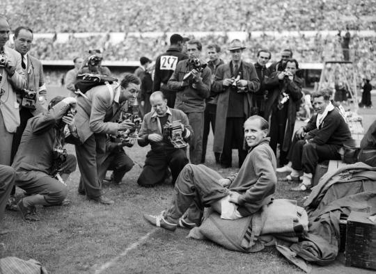Valokuvaajat ympäröivät istumassa olevaa Emil Zatopekia stadionilla.