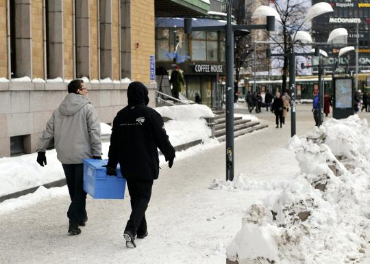 Kaksi miestä vie muuttolaatikkoa kävellen Postitalolta Voimataloon.