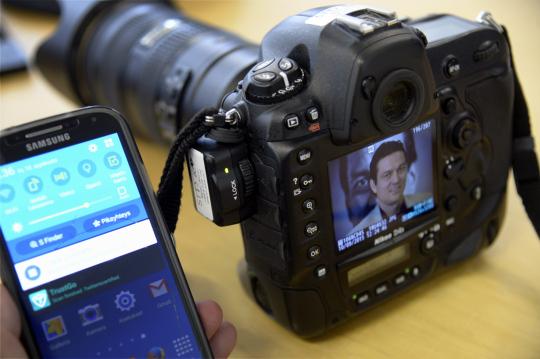 Pöydälle asetettu järjestelmäkamera ja matkapuhelin.