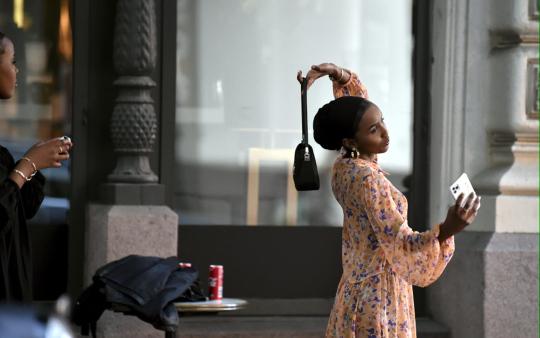 Nainen kuvaa itseään ja käsilaukkuaan kadulla.