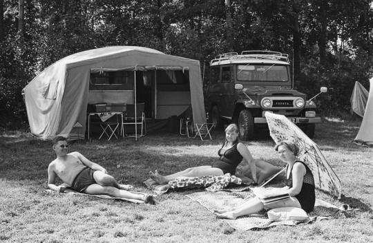 Lomaileva suomalaisperhe nauttii auringosta, taka-alalla auto ja matkailuvaunu.