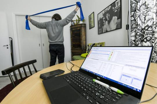 Kotona tietokoneella työskentelevä mies viettää taukoa kuminauhan avulla venytellen.