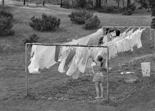 Nainen ripustaa pyykkiä kuivumaan pyykinkuivaustelineelle heinäkuussa 1973.