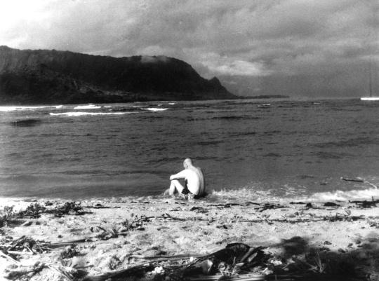 Presidentti Urho Kekkonen mietteissään rantahietikolla Havaijilla vuonna 1961.
